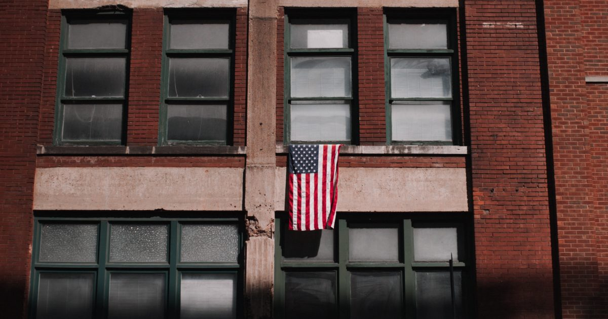 american flag hanging outside brick building