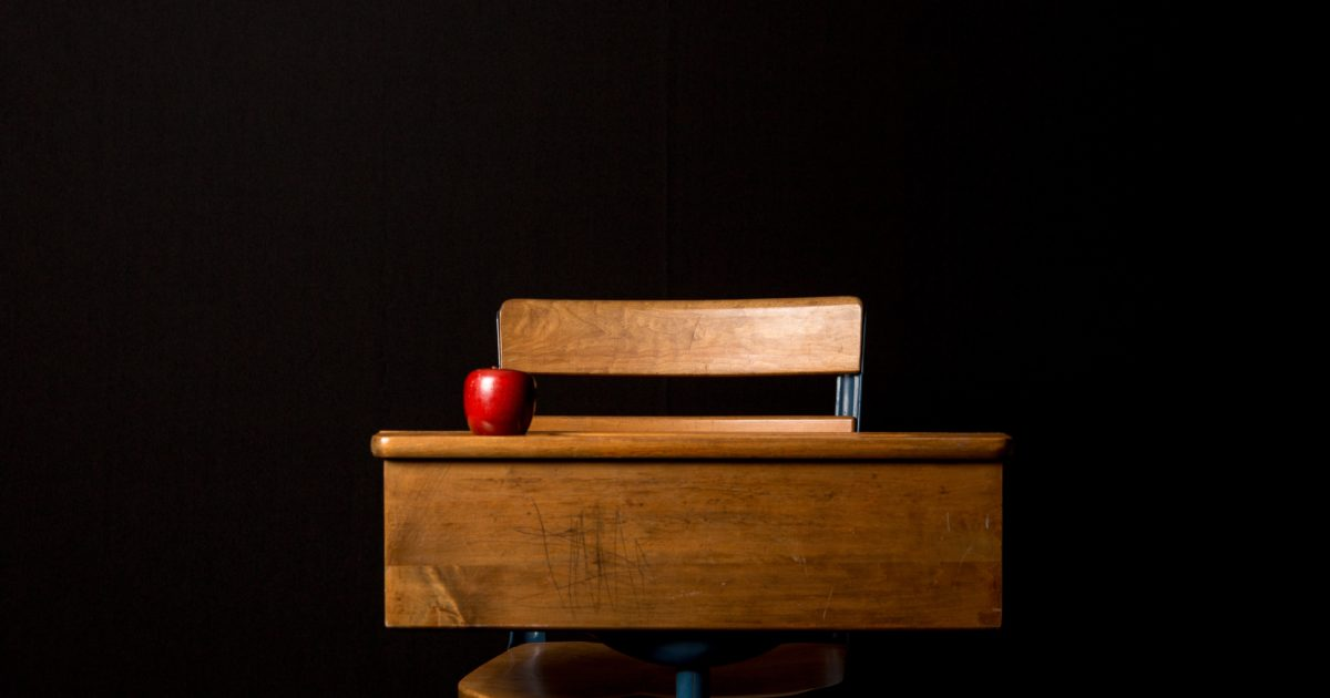 wooden school desk with apple